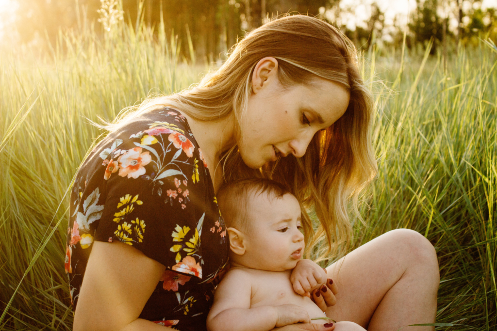 mom with baby in grassy field