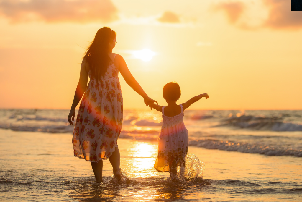 mom with child ocean sunset